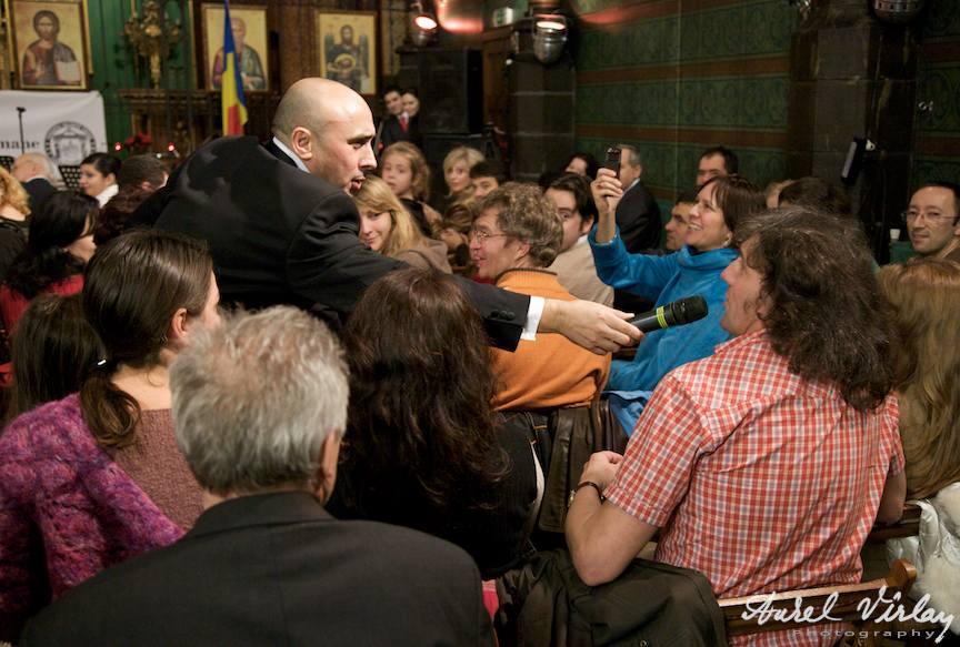 Fotografie cu Marcel Pavel oferind microfonul in sala de concert.