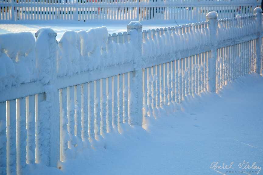 Soarele de apus fotografiat prin gardul plin de zapada