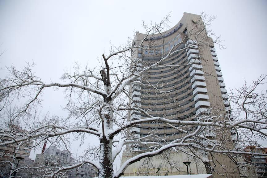 Hotelul Intercontinental Bucuresti vazut iarna printre crengile inzapezite.