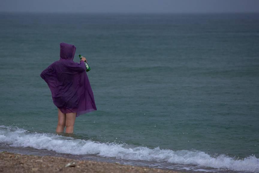 Singura femeie care testeaza apa marii pe timp de ploaie.