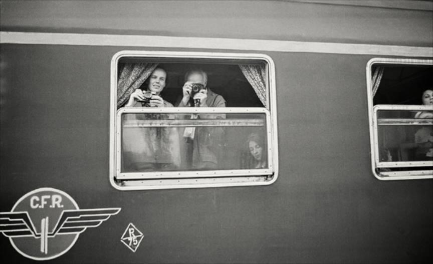 Martine Franck si Henri Cartier Bresson cu aparatele foto in maini la fereastra trenului.