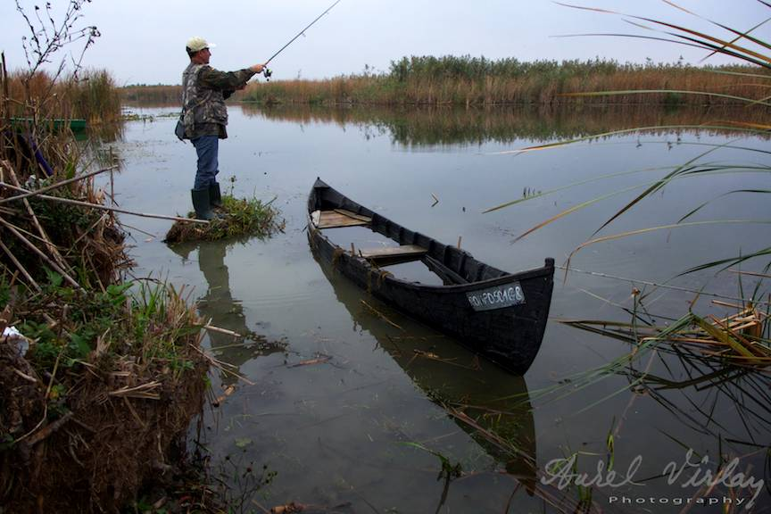 Peisaj foto cu pescar si barca din Delta Dunarii.