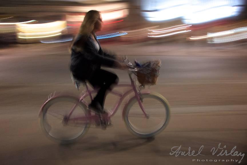 Fotografie in miscare urmarind o biciclista noaptea pe strazile Varsoviei.