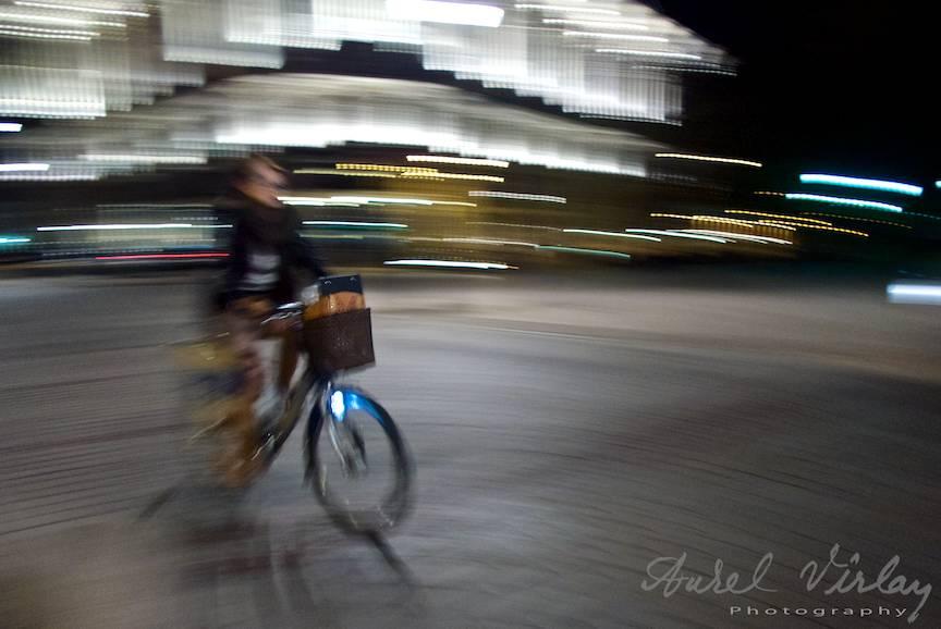 Fotojurnalism nocturn in plina miscare a unei biciclete pe fundal de Hotel Bristol.