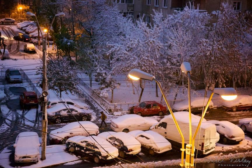 Copacii imbracati in alb de zapada sub luminile orasului.