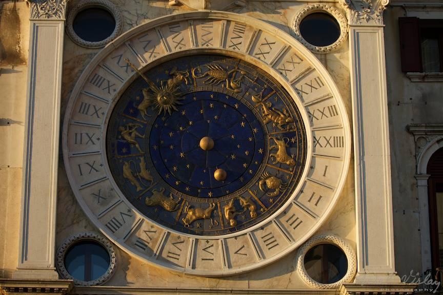 Detaliu foto cu orologiu din Piata San Marco sub lumina laterala a apusului de soare.