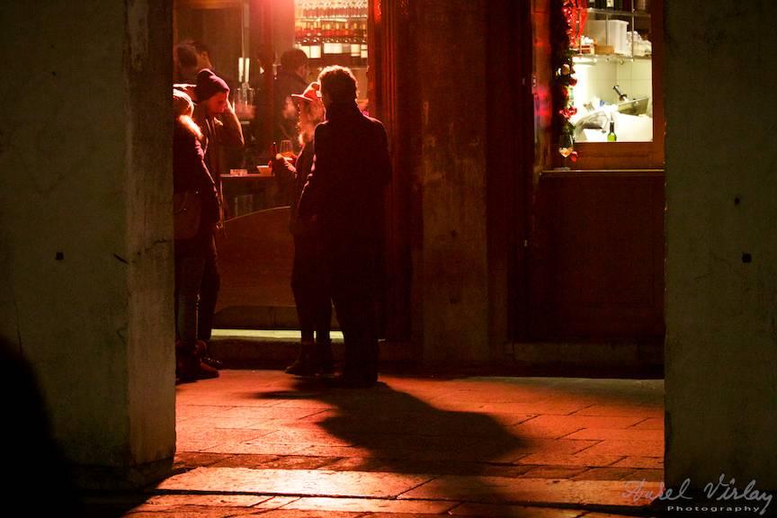 Fotografie de noapte la un spritz in lumina rosie a felinarelor venetiene.