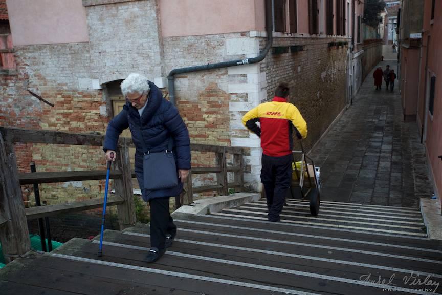 Batrana doamna cu baston albastru si curier DHL cu carutul pe treptele unui pod peste canale.