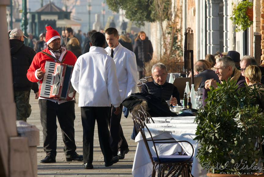 Tigan roman cu acordeon costumat in Mos Craciun, alungat de ospatarii venetieni.