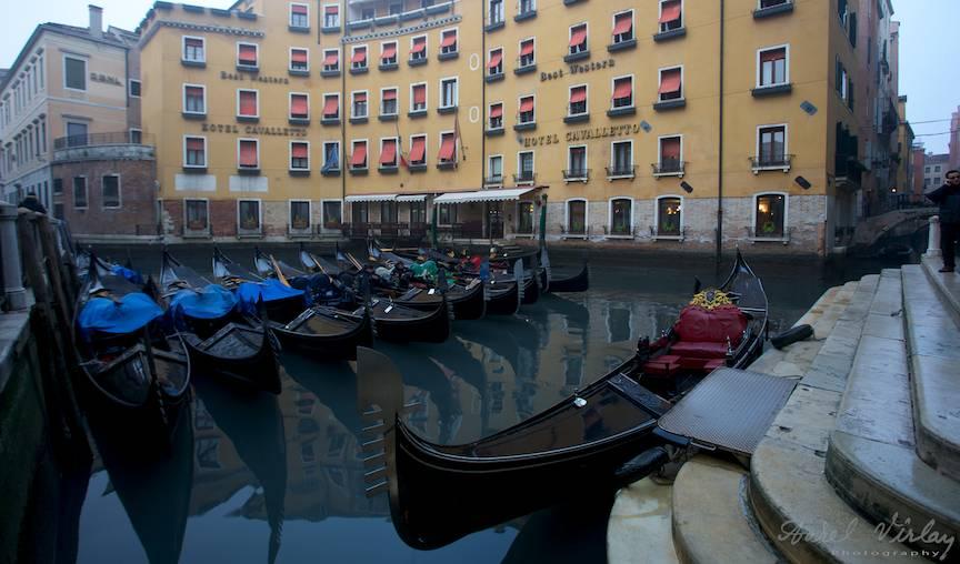 Peisaj citadin venetian cu gondole.