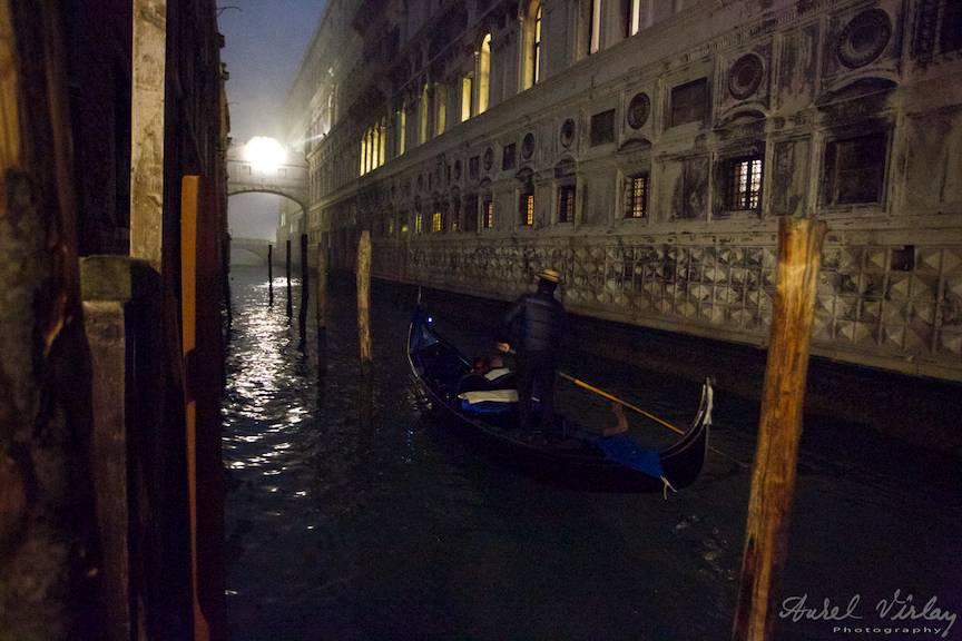 Fotografie nocturna cu o gondola ce va trece pe sub Puntea Suspinelor.