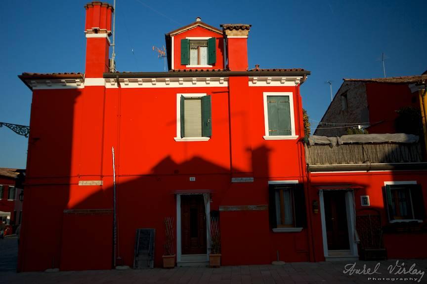 Iluzie fotografica al jocului umbrei aruncate pe casa rosie.
