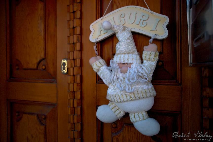 Auguri Christmas decoration la una din usile de lemn natural nevopsita din Burano.