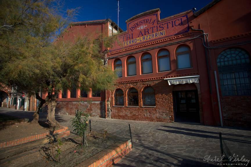 Fotografie arhitecturala cu fatada de caramida rosie a Fabricii de arta in sticlarie Murano.