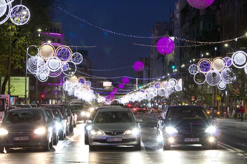 Masinile in trafic sub ploaia vesela de lumini colorate.