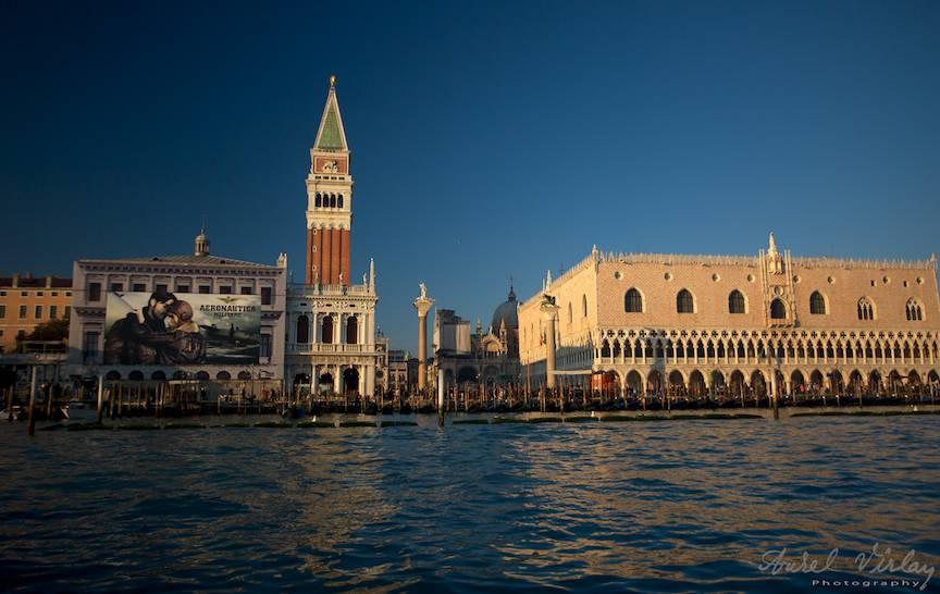 Fotografie emblematica cu Turnul din Piata San Marco si Palatul Dogilor in apus de soare.