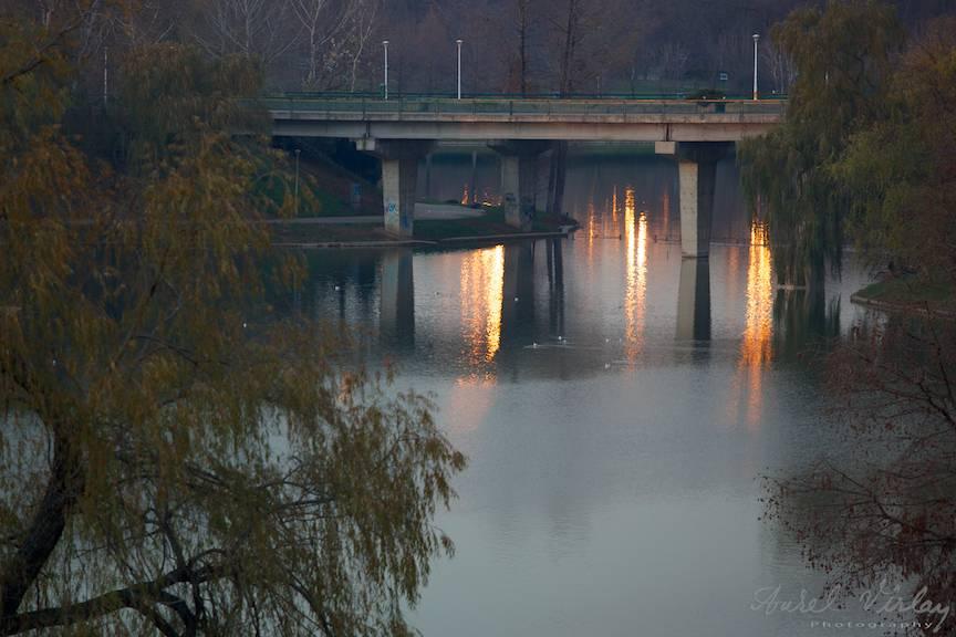 Reflexele aurii ale apusului de soare pe Lacul Tineretului.