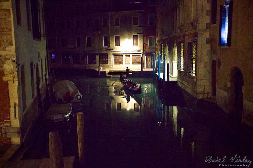 O gondola ratacita in miez de noapte imi ofera placerea unui peisaj foto nocturn pe un canal venetian.