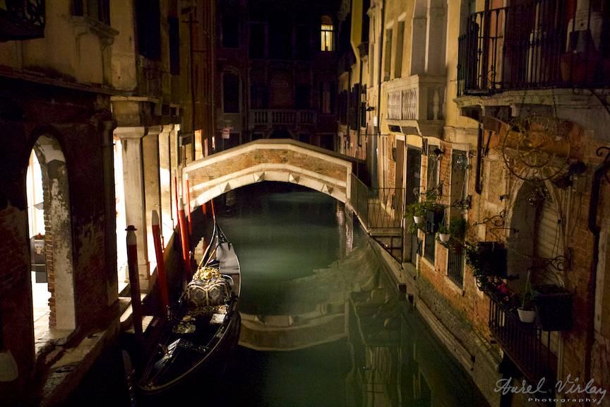 O gondola parcata noaptea langa un pod in frumoasa Venetie.