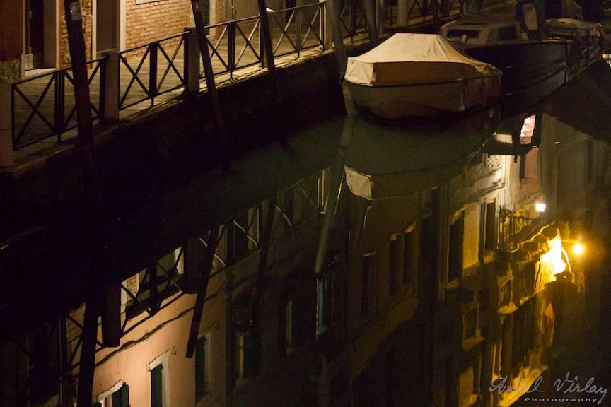 Fotografie aglindind odihna noptii si reflexe in apa din canalele venetiene.
