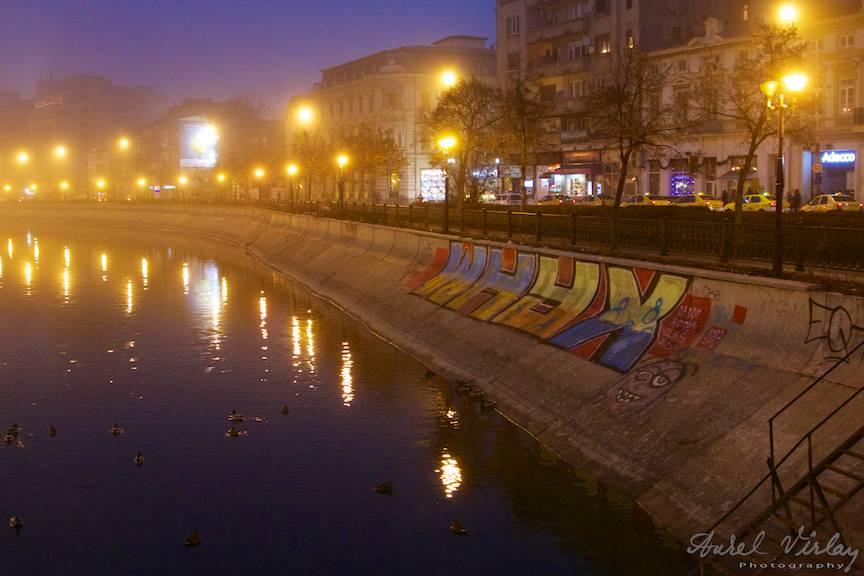 Peisaj foto citadin cu raul Dambovita traversand Bucurestiul.