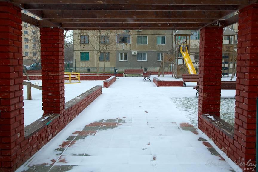 Fotografie in prima zi de ninsoare la locul de joaca dintre blocuri.