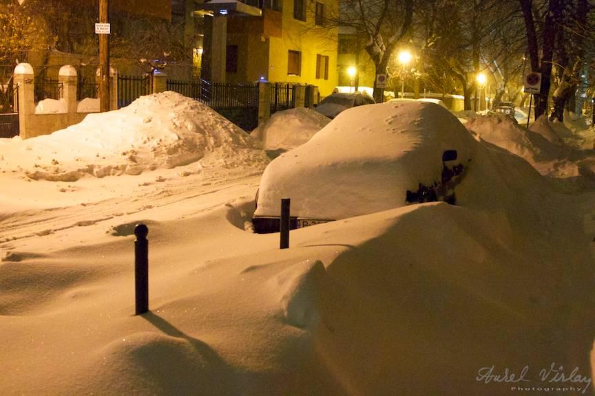 Fotografie de noapte cu troiene de zapada la lumina felinarelor.