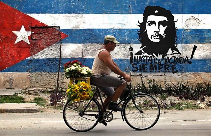 Instantaneu foto cu un biciclist pe langa pictura murala a rebelului Ernesto Che Guevara si steagul cubanez in Havana.