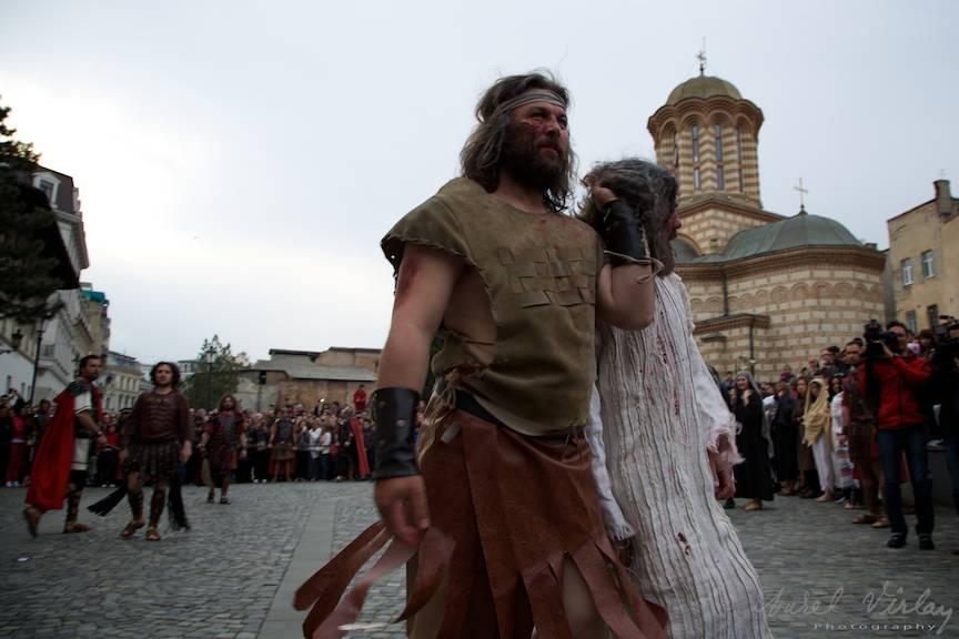 Fotojurnalism din scena condamnarii lui Iisus Hristos proiectata pe un fundal cu Biserica Sfantul Antonie cel Mare.