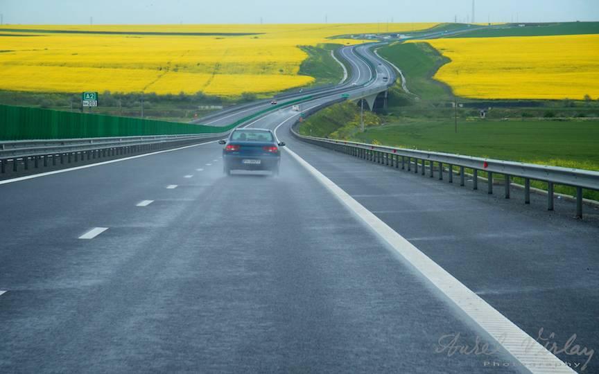 Autostrada Soarelui serpuind spre Marea Neagra printre lanuri galbene.
