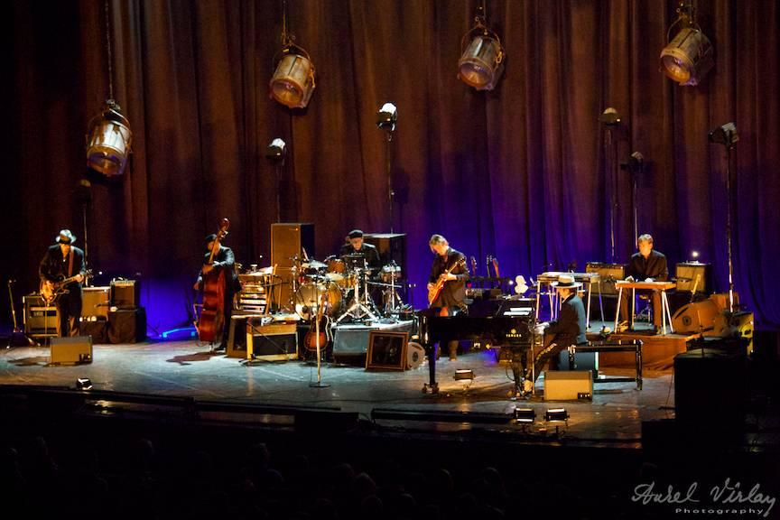 Bob Dylan la pian alaturi de trupa lui intr-o lumina teatrala.