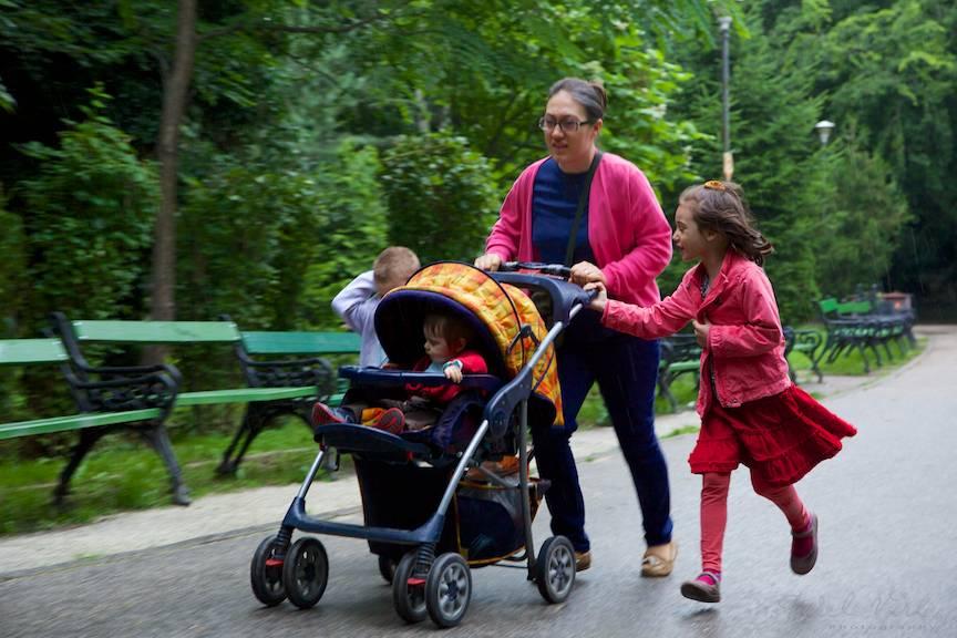 Fotoreportaj siclam: Doamna cu trei copii alergand prin ploaie.