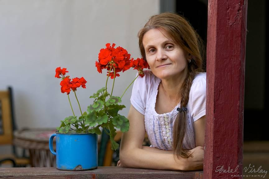 Portret de femeie langa o muscata din cerdac.