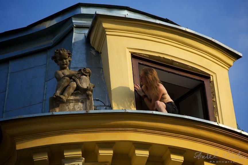 Apus de Soare peste o cladire veche, un turist si o statuie: doua personaje lunatice.