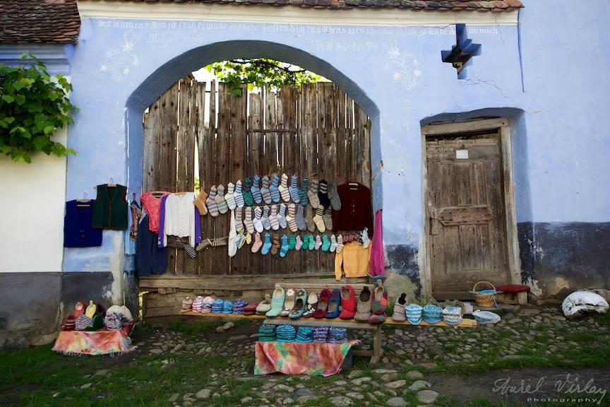 Peisaj rural cu haine si ciorapi impletiti de lana la o poarta saseasca.