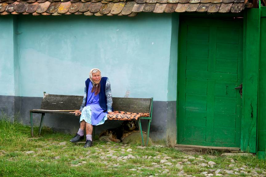 Tihna satului intr-o fotografie emblematica cu o batrana pe banca si cainele ei credincios.