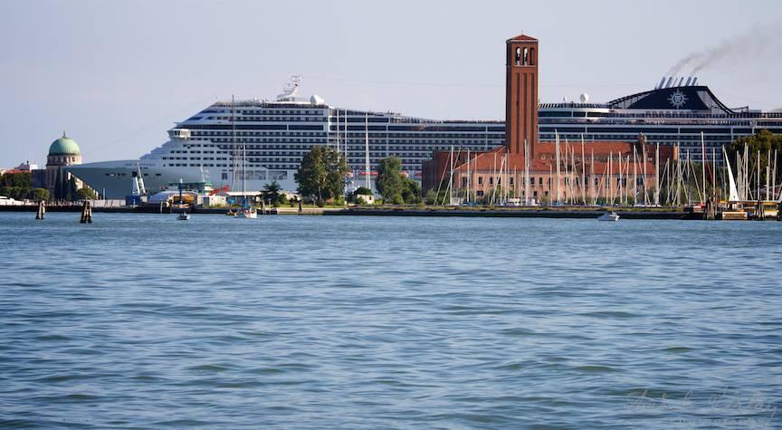 Peisaj foto citadin cu un monstru vapor de croaziera printre bisericile Venetiei.