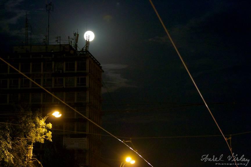 Peisaj citadin nocturn cu Luna Plina peste blocuri si felinare.